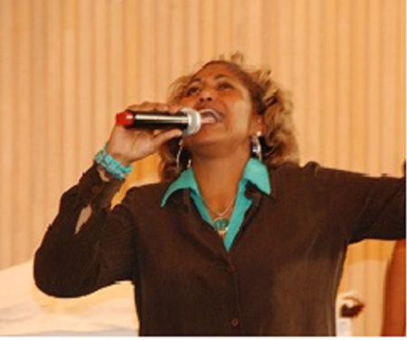 Minister Tracey singing in brown2